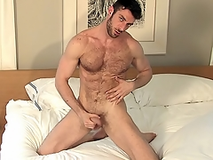He probes his asshole with his coal-black dildo all alone about bed